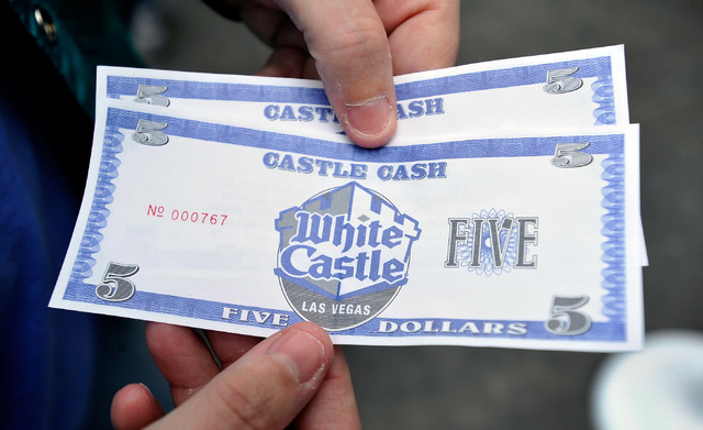 A customer displays White Castle's Castle Cash while standing in line before the grand opening of the restaurant's newest location on the Strip in Las Vegas on Tuesday, Jan. 27, 2015. (David Becke ...