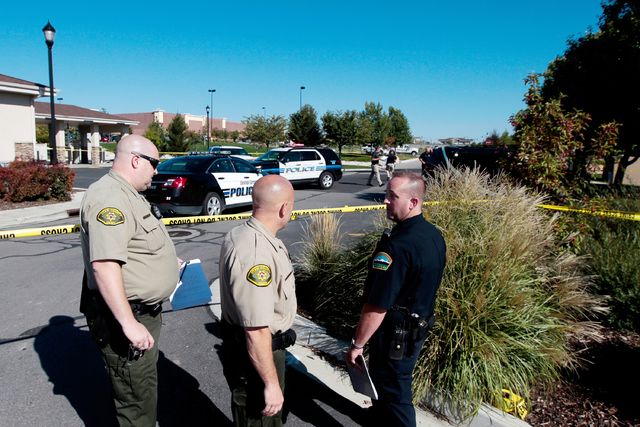 FILE - In this Sept. 10, 2014, file photo, police officers stand at the scene of a shooting in Saratoga Springs, Utah. Officials in Saratoga Springs, where a young black man was fatally shot by po ...