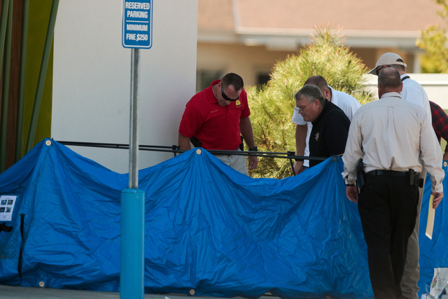 FILE - In this Sept. 10, 2014 file photo, law enforcement officals look at a body behind a tarp as they conduct an investigation at the scene of a shooting in Saratoga Springs, Utah. Officials in  ...