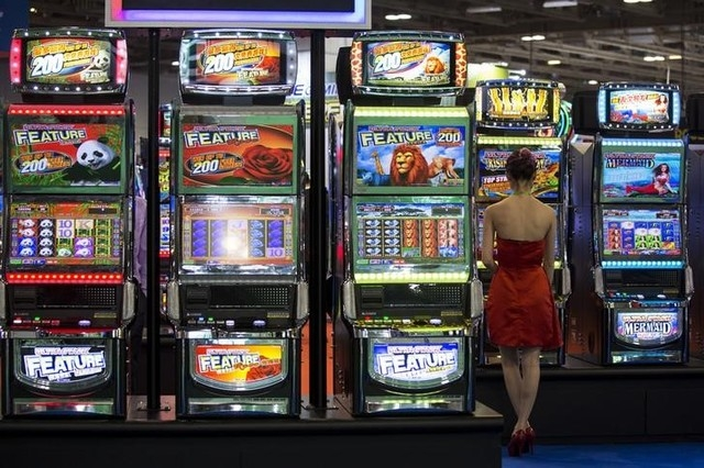A visitor tries a slot machine during the Global Gaming Expo Asia in Macau May 20, 2014. (REUTERS/Tyrone Siu)