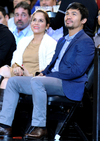 Professional boxer Manny Pacquiao, right, sits courtside during the first half of an NBA game between the Milwaukee Bucks and the Miami Heat at American Airlines Arena,Jan 27, 2015. Promoter Barb  ...