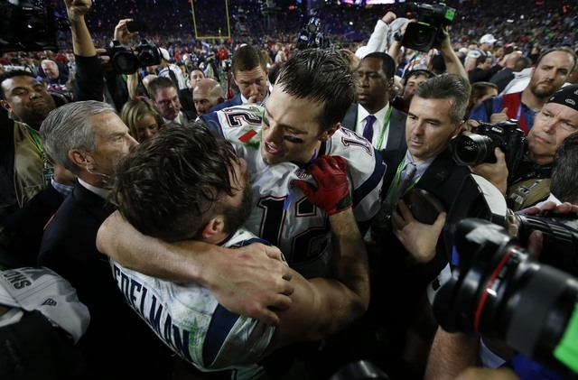 Feb 1, 2015; Glendale, AZ, USA; New England Patriots quarterback Tom Brady (rear) hugs wide receiver Julian Edelman (11) after defeating the Seattle Seahawks in Super Bowl XLIX at University of Ph ...