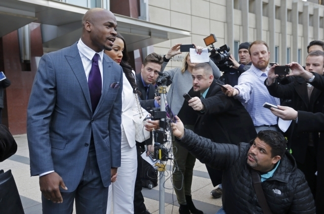 Minnesota Vikings running back Adrian Peterson addresses the media outside the U.S. District Courthouse with his wife, Ashley Brown Peterson, on Feb 6, 2015, as the NFL Players Association's lawsu ...