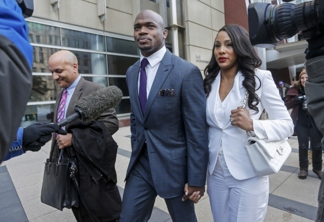 Minnesota Vikings running back Adrian Peterson leaves the U.S. District Courthouse with his wife, Ashley Brown Peterson, on Feb 6, 2015, as the NFL Players Association's lawsuit against the NFL on ...