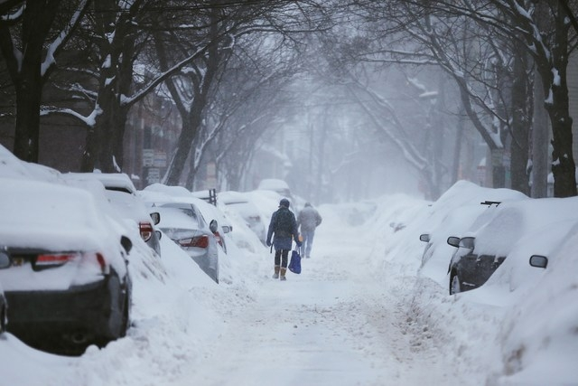 Pedestrians make their way along a snow covered street during a winter snow storm in Cambridge, Massachusetts February 9, 2015.  (REUTERS/Brian Snyder)