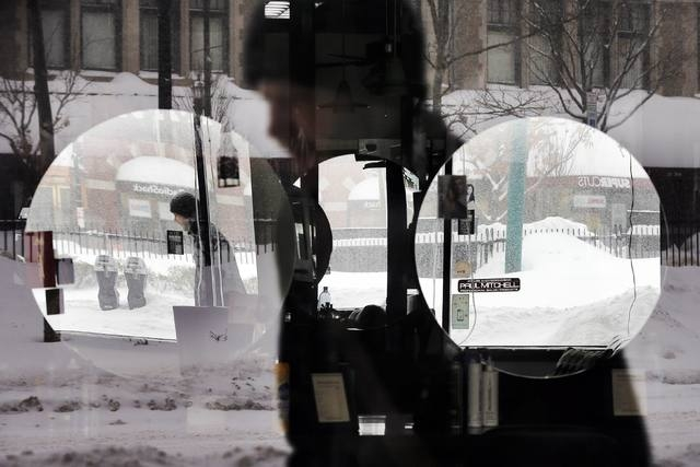A pedestrian is reflected in the window and mirrors of a hair salon during a winter snow storm in Brookline, Massachusetts February 9, 2015. (REUTERS/Brian Snyder)