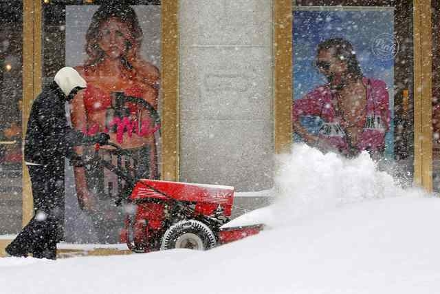 A worker clears the snow off the sidewalk in front of a Victoria's Secret store along a snow covered street during a winter snowstorm in Boston, Massachusetts February 9, 2015. (REUTERS/Brian Snyder)
