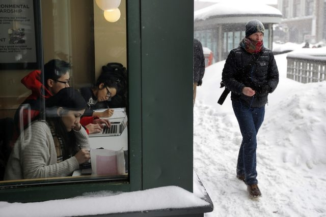 People work inside a Starbucks outlet during a winter snow storm in Cambridge, Massachusetts February 9, 2015. (REUTERS/Brian Snyder)