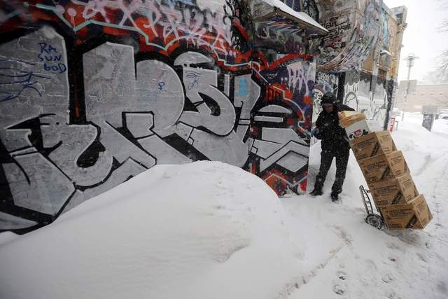 A worker makes a delivery during a winter snow storm in Cambridge, Massachusetts February 9, 2015. (REUTERS/Brian Snyder)