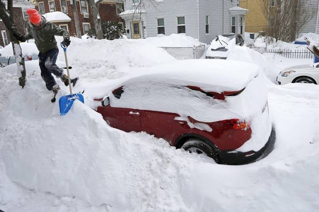 Greg Burkett clears snow from the front of his house during a winter snowstorm in Cambridge, Massachusetts February 9, 2015.  (REUTERS/Brian Snyder)