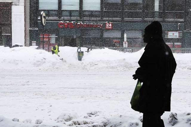 A man waits in a bus shelter during a winter snow storm in Cambridge, Massachusetts February 9, 2015. (REUTERS/Brian Snyder)