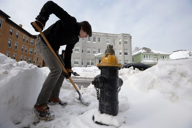 Elijah Childs, who came out to help clear snow around busy school routes at the request of the activist group Black Lives Matter Boston, shovels around a fire hydrant on Humboldt Ave in Boston, Ma ...