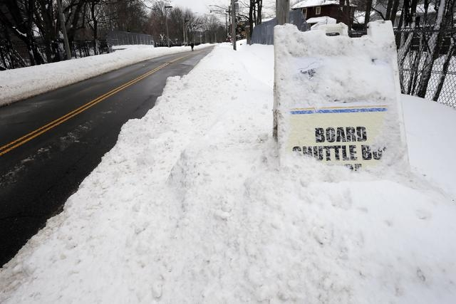 A sign in a snow drift marks the shuttle bus service at the closed MBTA subway station in Boston, Massachusetts February 10, 2015. (REUTERS/Brian Snyder)