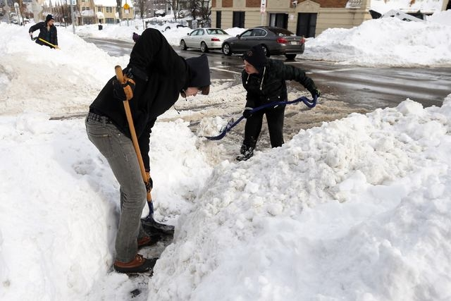 Volunteers, who came out to help clear snow around busy school routes at the request of the activist group Black Lives Matter Boston, shovel a sidewalk on Humboldt Ave in Boston, Massachusetts Feb ...