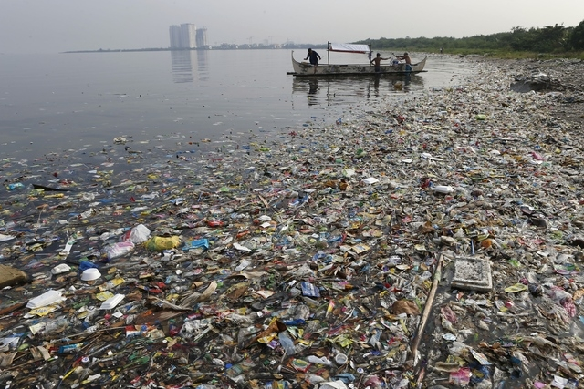 Fishermen prepare to fish, amidst floating garbage off the shore of Manila Bay during World Oceans Day in Paranaque, Metro Manila in this June 8, 2013 file photo.  Scientists estimate that a stagg ...