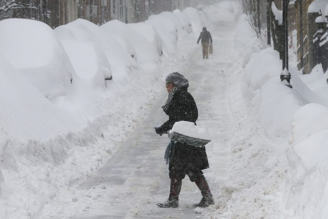 A woman shovels snow on Joy Street during a winter blizzard in Boston, Massachusetts February 15, 2015. (REUTERS/Brian Snyder)