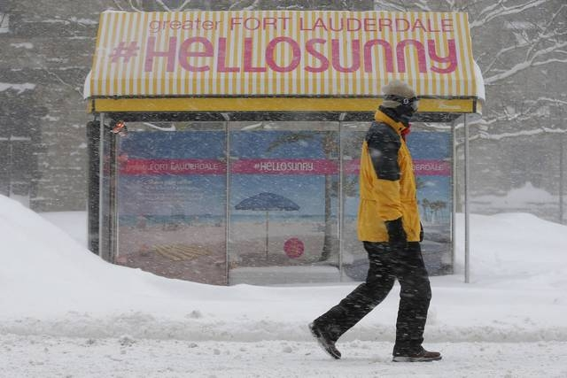 A pedestrian walks past a bus stop with an advertisement for Florida during a winter blizzard in Boston, Massachusetts February 15, 2015. (REUTERS/Brian Snyder)