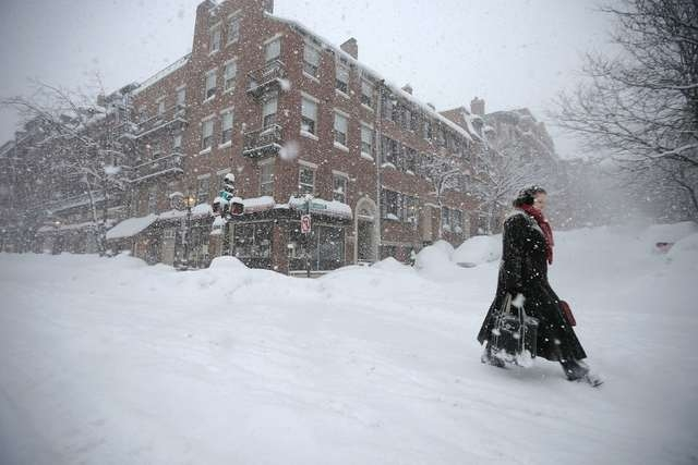 A woman walks through the snow down Charles Street during a winter blizzard in Boston, Massachusetts February 15, 2015. (REUTERS/Brian Snyder)