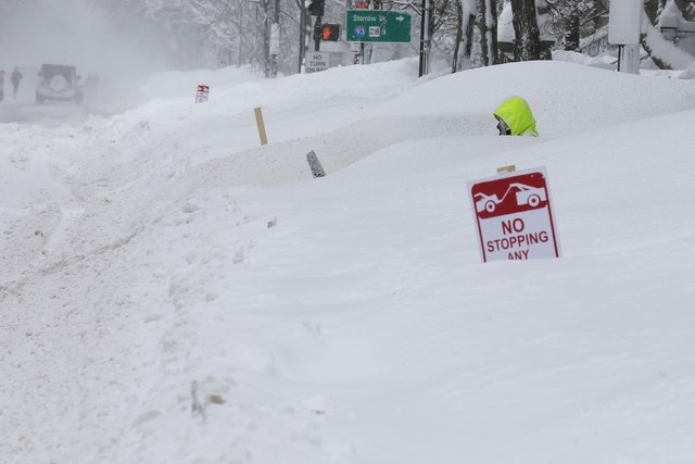 A worker cuts a path through the large snow mounds with a snowblower on Beacon Street during a winter blizzard in Boston, Massachusetts February 15, 2015. (REUTERS/Brian Snyder)