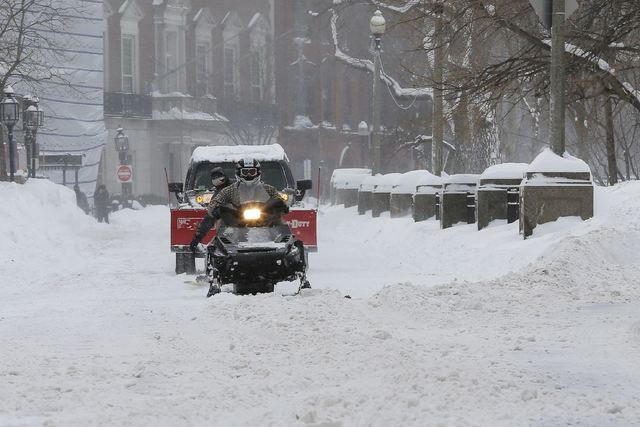 A snow-mobile pulls a man on snow board on Commonwealth Avenue in Boston, Massachusetts following a winter storm February 15, 2015. (REUTERS/Brian Snyder)