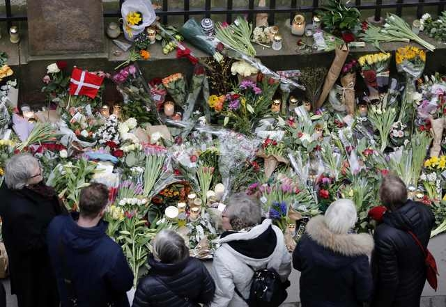 People pause for a moment of silence at a memorial site for the victims of the deadly attacks in front of the synagogue in Krystalgade in Copenhagen, February 16, 2015. The shootings, which Prime  ...
