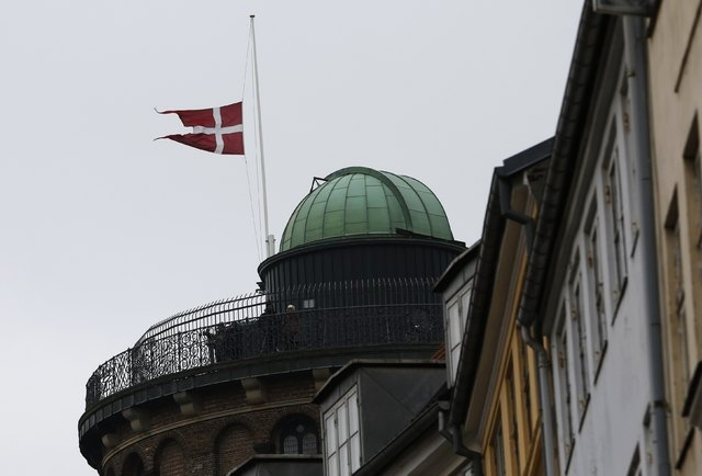 The Danish flag is seen at half-mast next to a memorial site for the victims of the deadly attacks in front of the synagogue in Krystalgade in Copenhagen, February 16, 2015. The shootings, which P ...