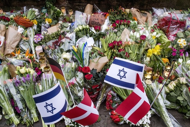 Floral tributes are placed at the site, where a Danish Jew was shot dead as he stood guard at a Jewish confirmation at the weekend, in front of the synagogue in Krystalgade, Copenhagen, February 1 ...
