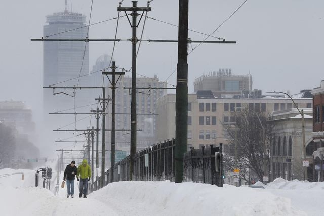 Pedestrians walk along snow covered, MBTA subway rails on Commonwealth Avenue in Boston, Massachusetts following a winter storm February 15, 2015.   (REUTERS/Brian Snyder)
