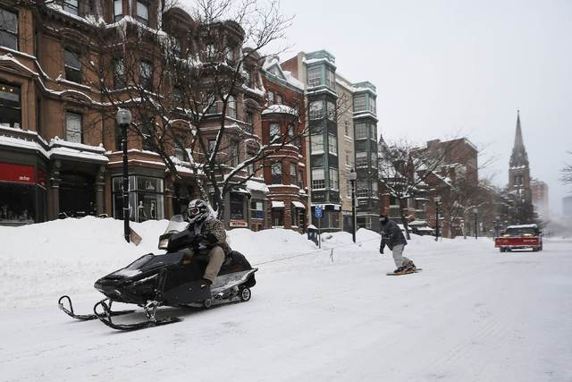 A snowmobile pulls a man on snow board on Newbury Street in Boston, Massachusetts following a winter storm February 15, 2015. (REUTERS/Brian Snyder )