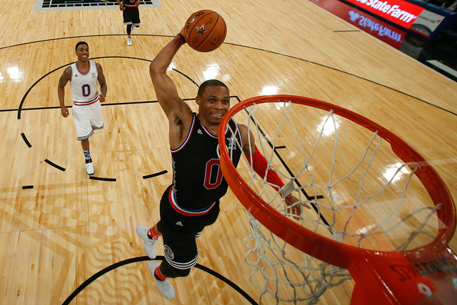 February 15, 2015; New York, NY, USA; Western Conference guard Russell Westbrook of the Oklahoma City Thunder (0, right) dunks the basketball ahead of Eastern Conference guard Jeff Teague of the A ...