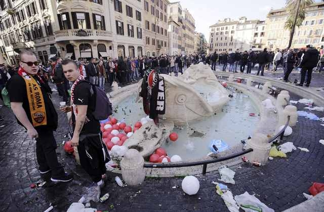 """Feyenoord fans stand next to the fountain called """"Barcaccia"""", made by Pietro Bernini, during clashes with police prior to the start of the Europa League soccer match between Roma and Feyenoord, at ..."""