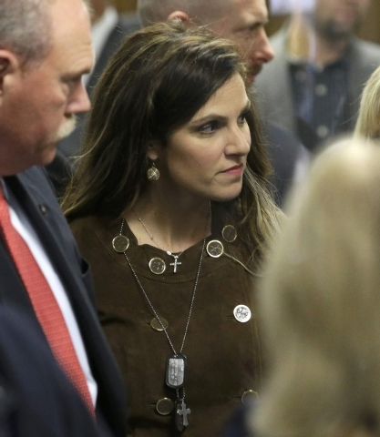 Taya Kyle, widow of former Navy SEAL Chris Kyle, wears her husband's military dog tags as she walks out of the courtroom during a break in the capital murder trial of former Marine Eddie Ray Routh ...