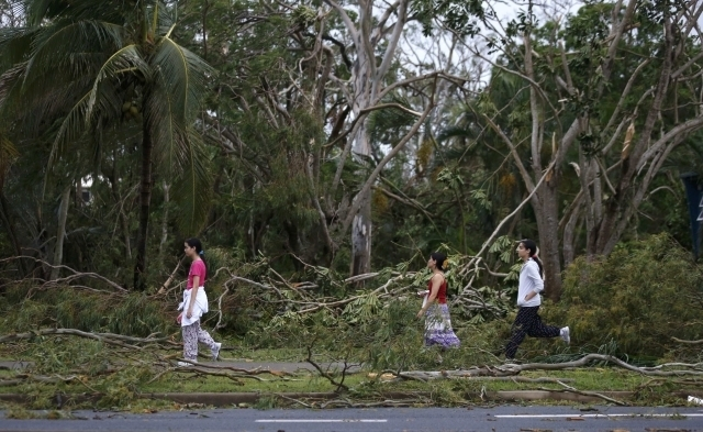Residents of the coastal town of Yeppoon step through fallen trees alongside a damaged home after Cyclone Marcia hit northeastern Australia, Friday, Feb. 20, 2015. Marcia slammed into northeast Au ...