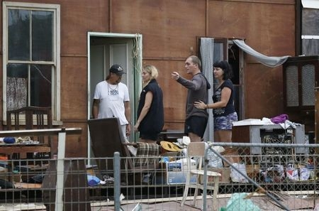 Members of the Cobb family observe the damage to what used to be a room in their grandmother's house after Cyclone Marcia hit the coastal town of Yeppoon in northeastern Australia, Friday, Feb. 20 ...