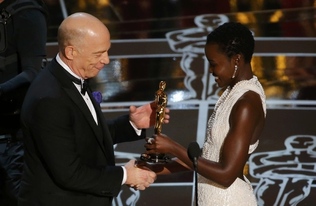 """J.K. Simmons receives the Oscar for actor in a supporting role for """"Whiplash"""" from presenter Lupita Nyong'o  at the 87th Academy Awards in Hollywood, California February 22, 2015. (REUTERS/Mike Blake)"""