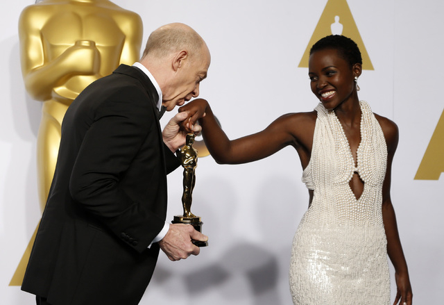 """J.K. Simmons, winner of the award for best supporting actor nominee for his role in """"Whiplash,"""" kisses the hand of presenter Lupita Nyong'o during the 87th Academy Awards in Hollywood, California  ..."""