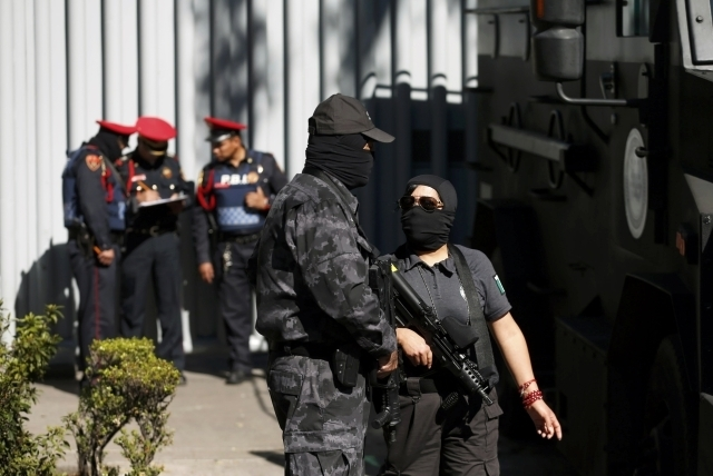 Federal police officers stand outside the building housing the Assistant Attorney General's Office for Special Investigations on Organized Crime in Mexico City, Friday, Feb. 27, 2015. Mexico has c ...