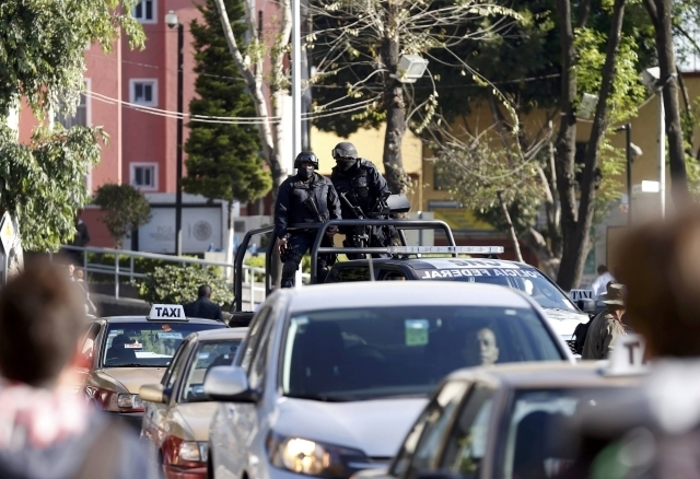 Federal police officers stand on the back of a pick-up truck while driving through the traffic outside the building housing the Assistant Attorney General's Office for Special Investigations on Or ...