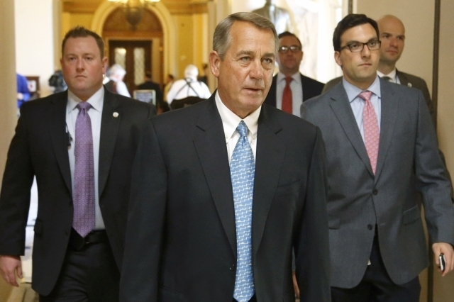 U.S. House Speaker John Boehner, R-Ohio, center, returns to his office after a visit to the House floor for procedural votes for legislation to fund the Department of Homeland Security at the Capi ...