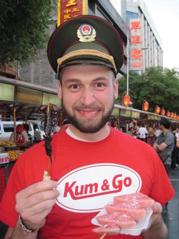 James Henderson eats a scorpion at Wangfujing.
