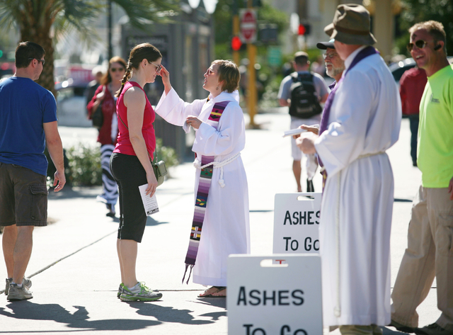 The Rev. Erin Hutchison, center, applies ashes to the forehead of Traci Barnett, of Buffalo, N.Y., on the sidewalk along the Strip near The Mirage on Wednesday. Christ Church Episcopal clergy memb ...