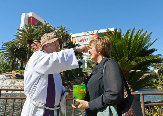 The Rev. Barry Vaughn, left, applies ashes to the forehead of Cheryl Aldrich, of North Dighton, Mass., on the sidewalk along the Strip near The Mirage on Wednesday. Christ Church Episcopal clergy  ...