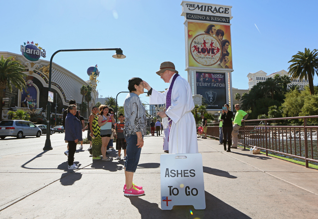 The Rev. Barry Vaughn, right, applies ashes to the forehead of Lilia Peche on the sidewalk along the Strip near The Mirage on Ash Wednesday. (Ronda Churchill/Las Vegas Review-Journal)