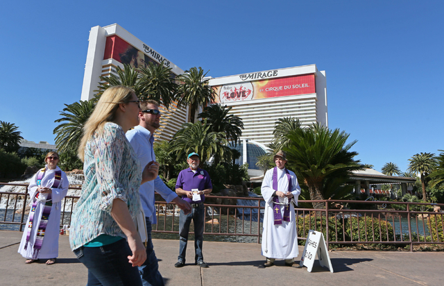 Pedestrians walk past the Rev. Erin Hutchison, from left, Richard Corson and the Rev. Barry Vaughn on the sidewalk along the Strip near The Mirage on Wednesday. Christ Church Episcopal clergy memb ...