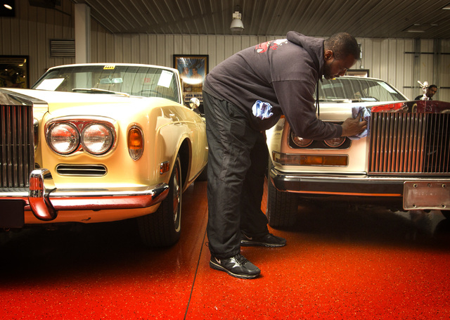 Steven Bruce details a 1972 Rolls Royce Camague at the Rogers' Classic Car Museum, 1480 Gragson Avenue, on Tuesday, Feb. 3, 2015. On the left is a 1972 Rolls-Royce Corniche Convertible. (Jeff Sche ...