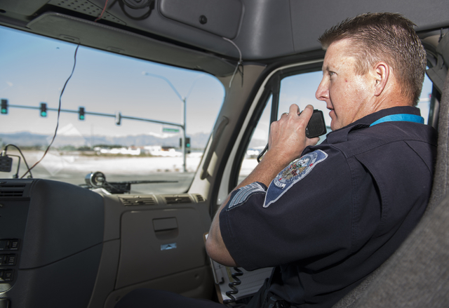 Sgt. Michael Cooke of the Nevada Highway Patrol communicates to other officers the violations he observes as he rides along in a tractor-trailer rig during the Badge on Board program launched by t ...