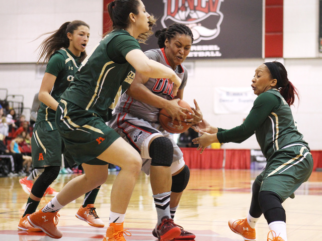 UNLV guard Amie Callaway drives between Colorado State forward Alana Arias, left, and guard A.J. Newton during their Mountain West Conference Game Saturday, Feb. 7, 2015, at the Cox Pavilion. Colo ...