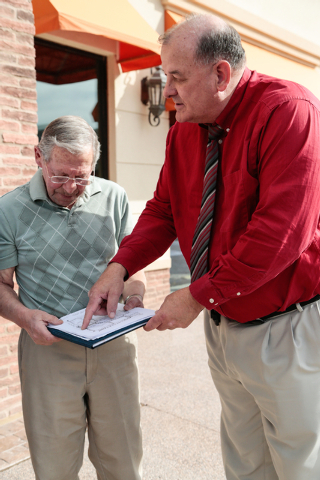 Residents association president Mike Micone, left, holds a clipboard while the general manager of Sun City McDonald Ranch, Ron Winkel, points on a map to areas affected by a proposed new campus fo ...