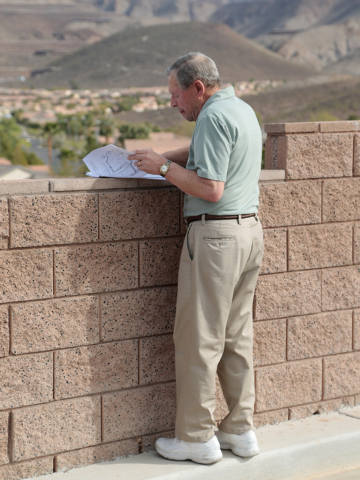 Residents association president Mike Micone looks at a map for the proposed Coral Academy of Science's new campus while standing in front of the wall that borders the homes and the campus at West  ...