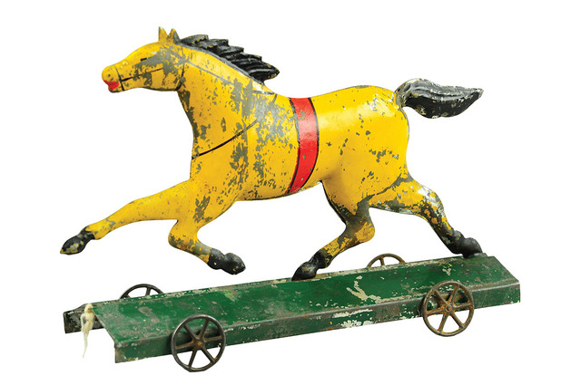 Cowles Syndicate Dexter, the toy horse on a platform, is 9 inches long. The rare tin toy was made about 1880 by George Brown, a famous toy maker from Connecticut.